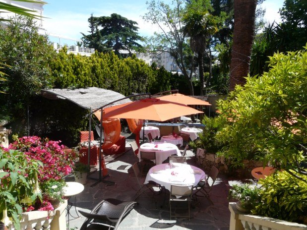 Hotel Alexandra garden with orange parasols over tables and greenery and flowers