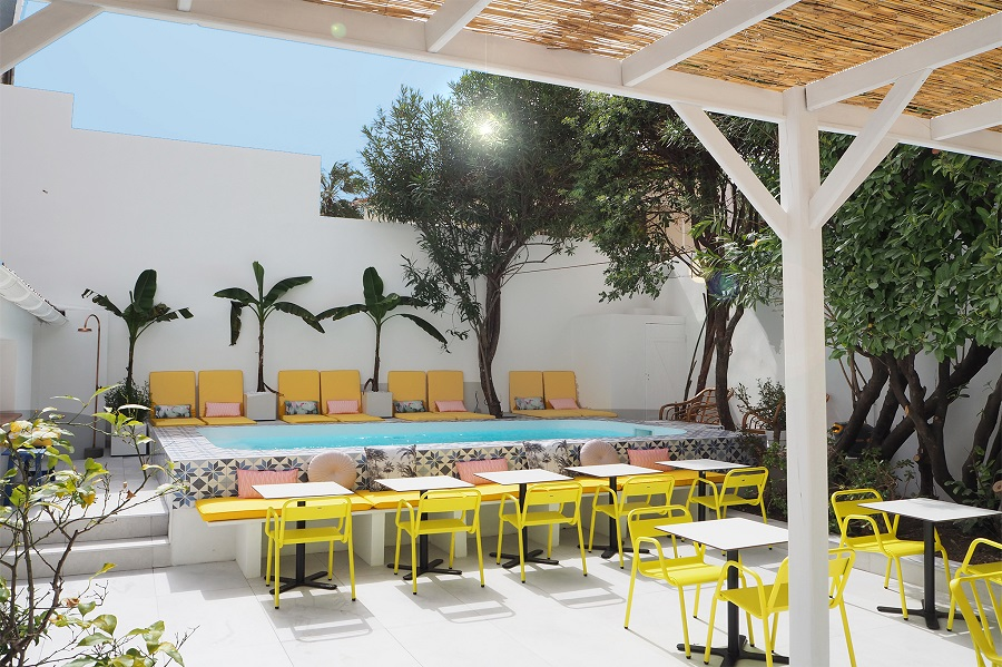 Hotel Mademoiselle pool with yellow tchairs and tables and covering