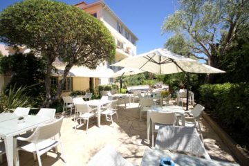 Beau Site Hotel garden with white parasols, tables and chairs