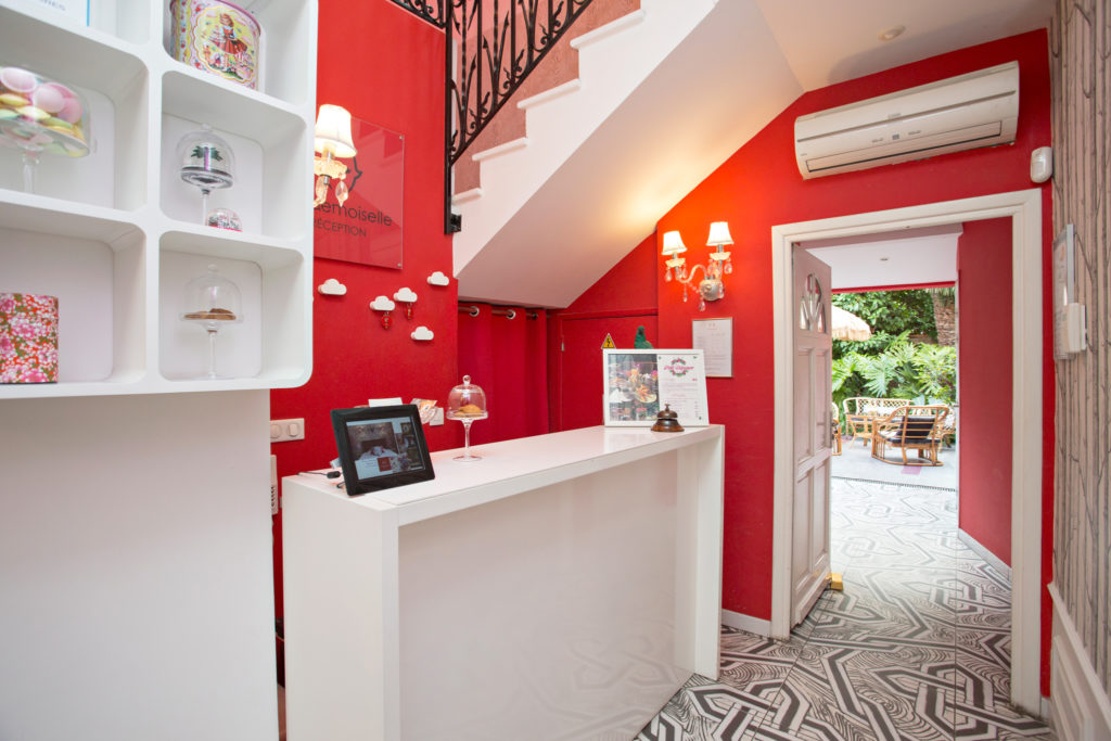 Hotel Mademoiselle hallway with bright red walls, funky decorations and view to the garden