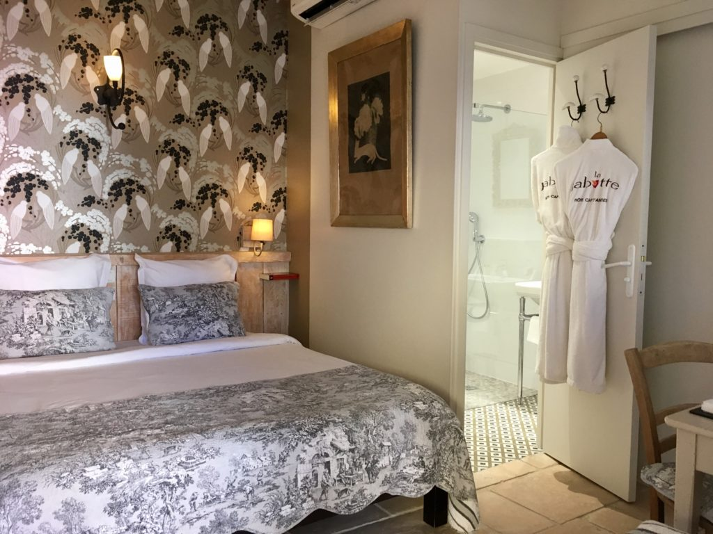 La Jabotte Hotel room with pretty patterned wallpaper and different bed coverings looking into the bathroomok