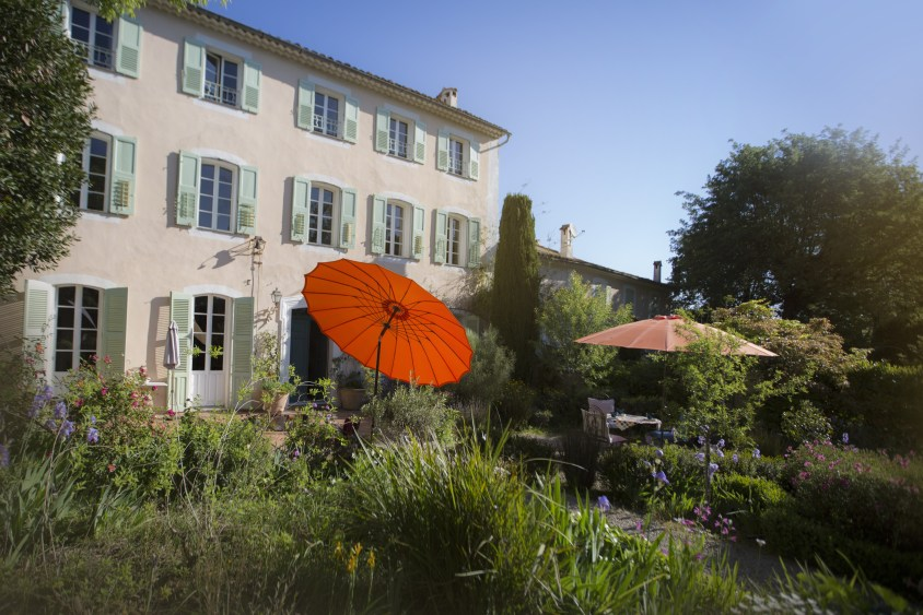 la bastide b&b in Antibes garden with house in background and red parasol