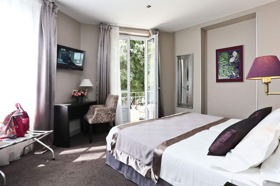 La Place Hotel Antibes room with small french windows onto balcony and pretty lilac and pale mauve colours