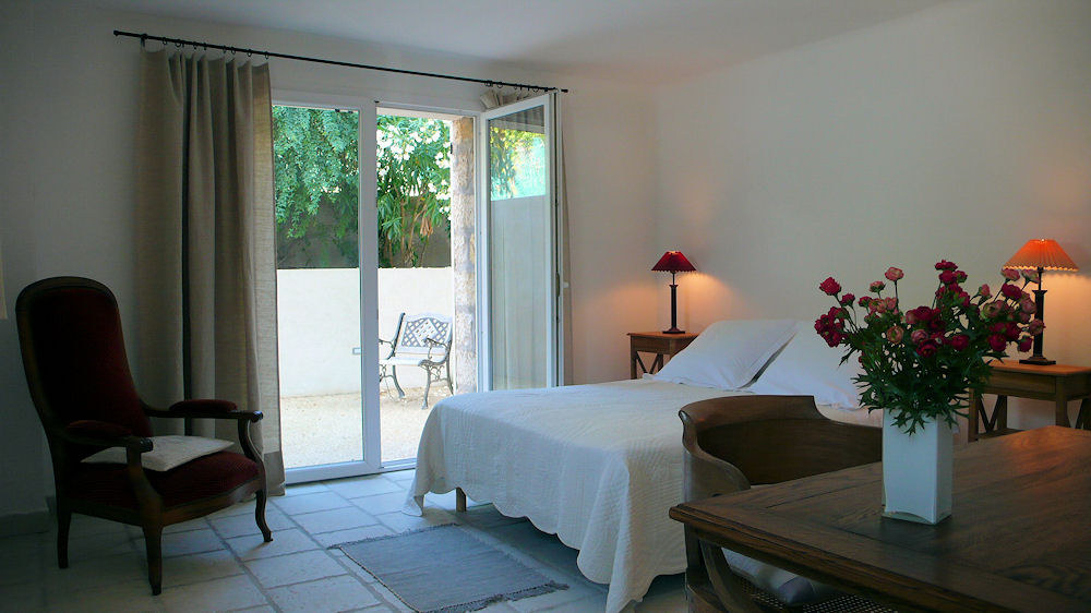 Villa Plein Soleil Juan les Pins bedroom in light colours looking out through french windows onto patio