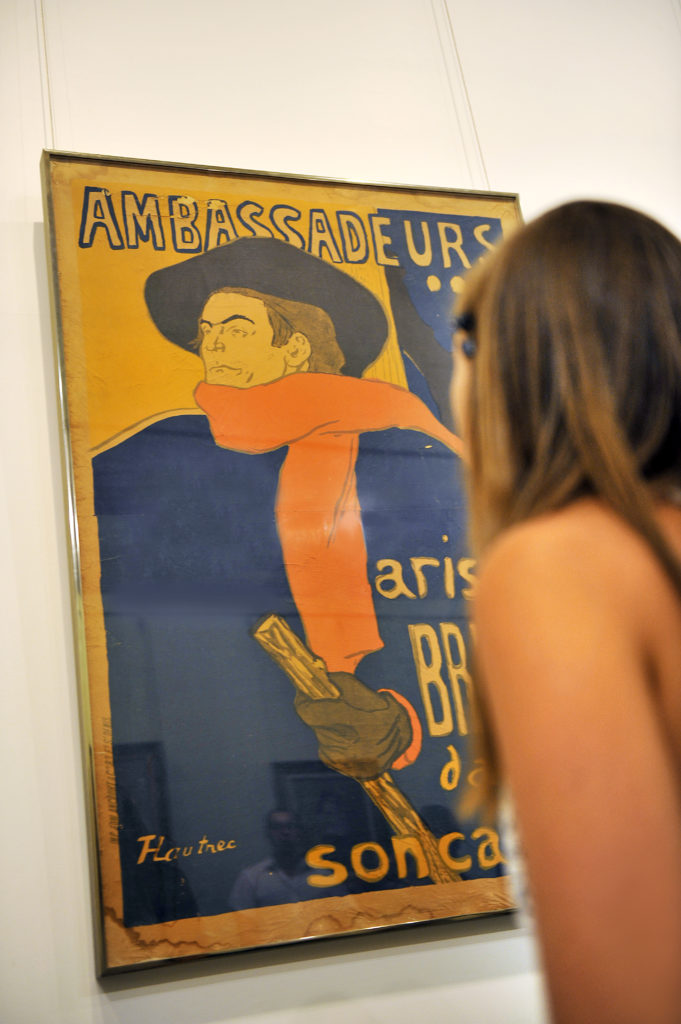 Woman standing in front of Aristide Bruant Toulouse-Lautrec poster at the Toulouse-Lautrec Museum