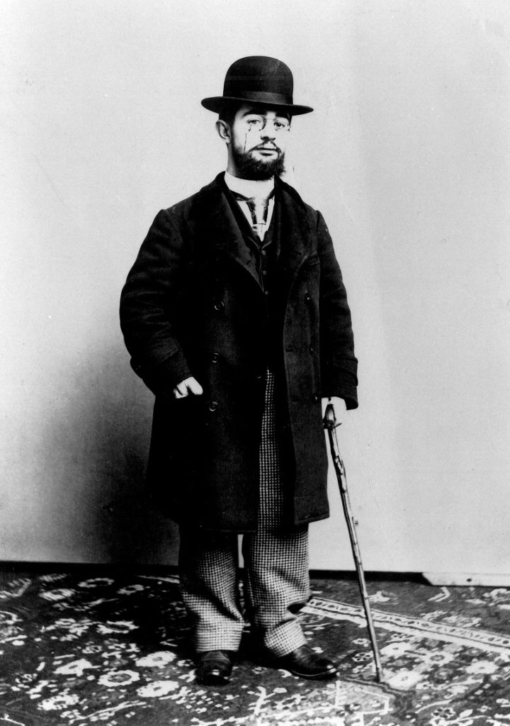 Black and white photo of Toulouse-Lautrec in 1892 with bowler, black coat and cane