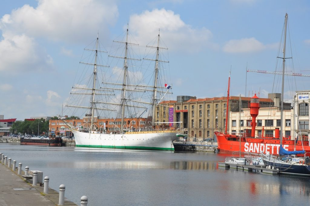 View over water of tall ship and Dunkirk's Maritime Museum in background